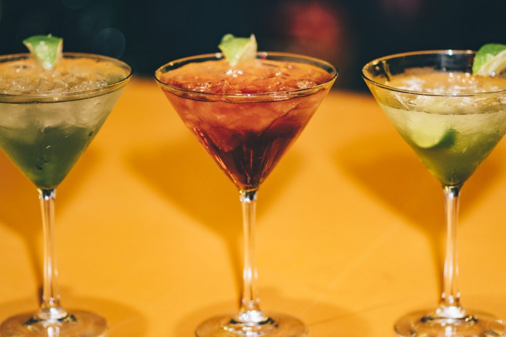 three colourful martinis in a line on an orange table