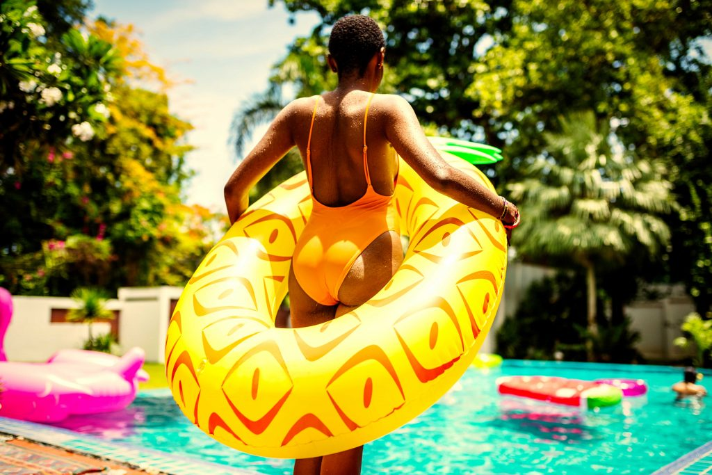 a woman standing by the pool with a pineapple floatie
