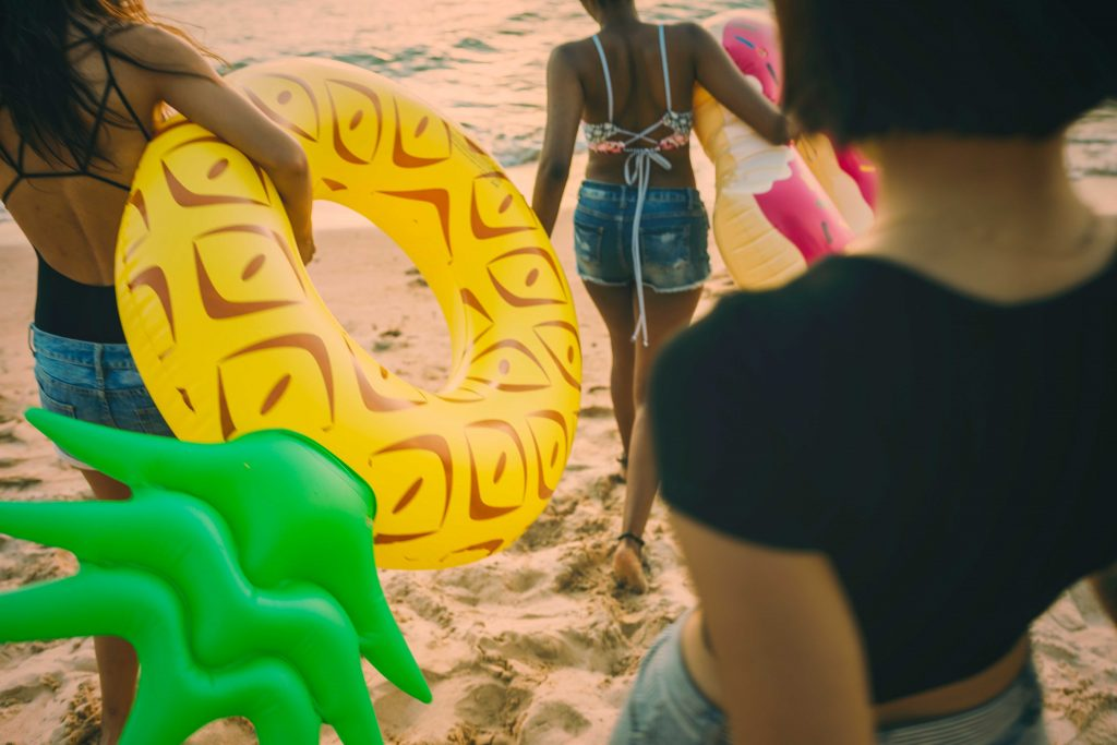 group of women walking at the beach with floaties
