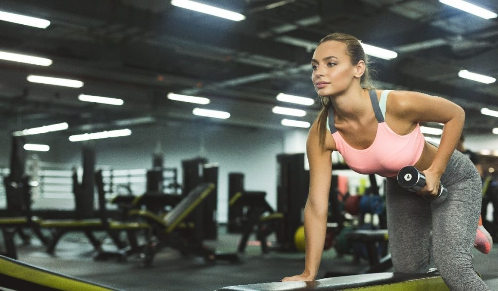 woman-holding-dumbbell-leaning-on-a-workout-bench
