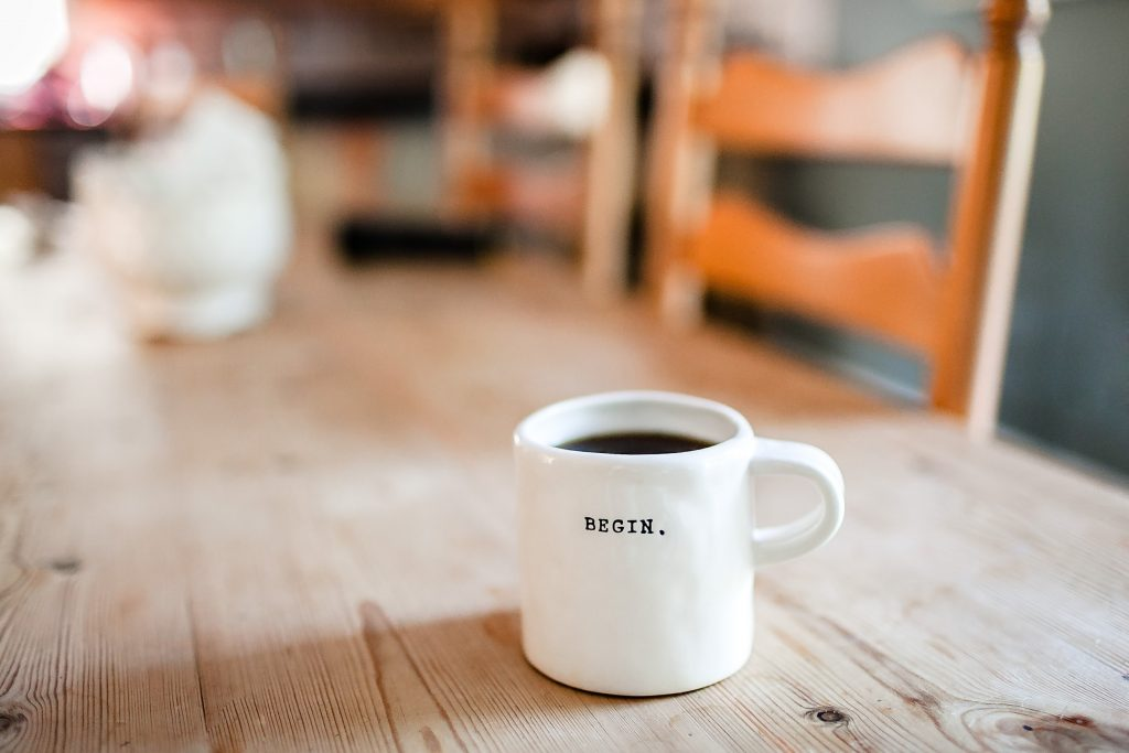 a white coffee mug with the word begin on it