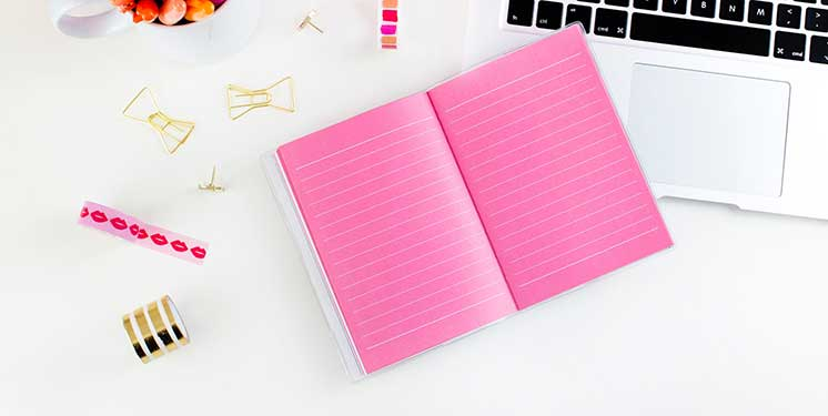 pink notebook with a laptop and colourful pens 746x375