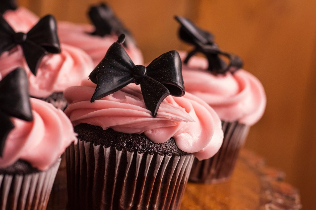 cupcakes with pink frosting and a chocolate bow